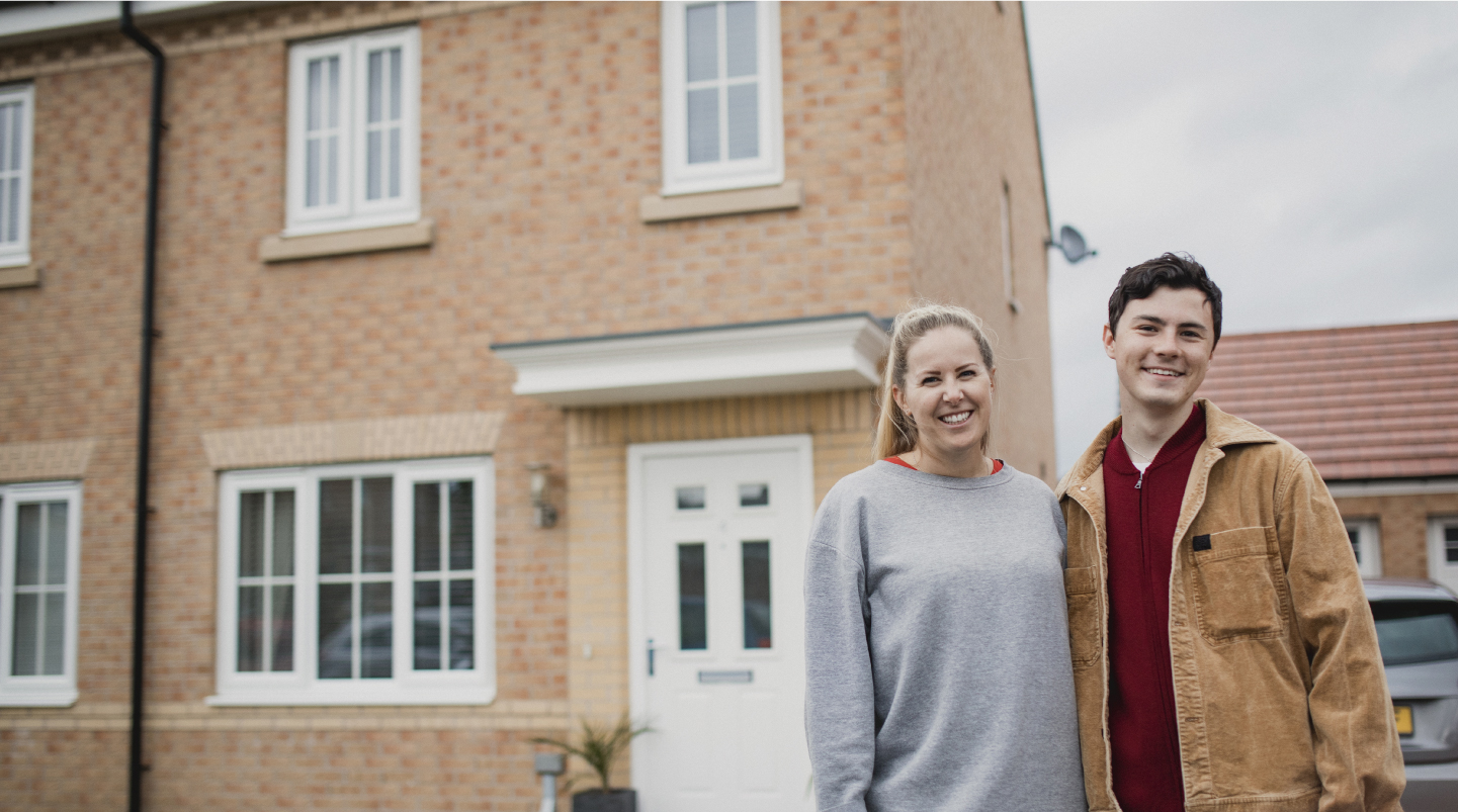 first time buyers standing in front of new home